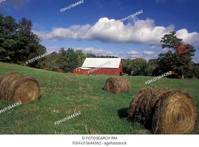 autumn, Vermont, Hay bales in green field with red barn and blue sky with puffy white clouds in the fall in Peacham in Caledonia County in the state of Vermont