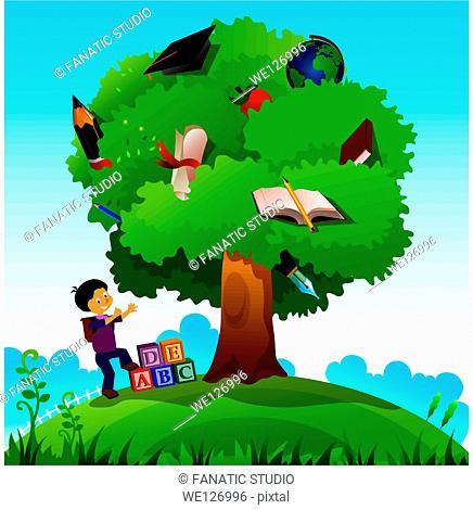 Schoolboy standing near a knowledge tree