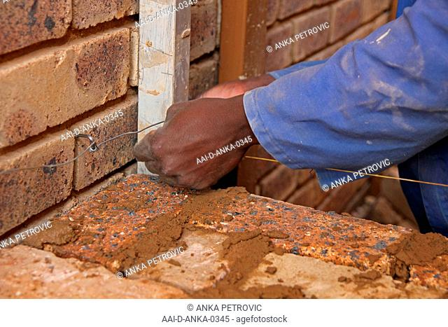 Brick layer laying bricks, close-up of hands, Moreleta Park, Pretoria, Gauteng Province, South Africa