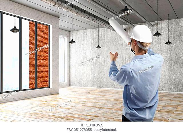 Young engineer pointing at something in grunge interior with city view. Architect concept. 3D Rendering