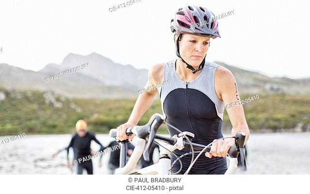 Woman pushing bicycle on beach