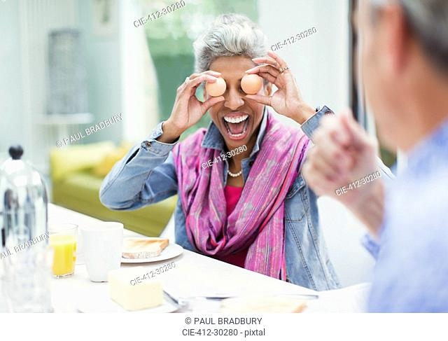 Playful mature woman covering eyes with eggs at breakfast table