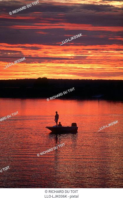 Fishing at dawn with a dramatic sunrise, Chobe River, Namibia