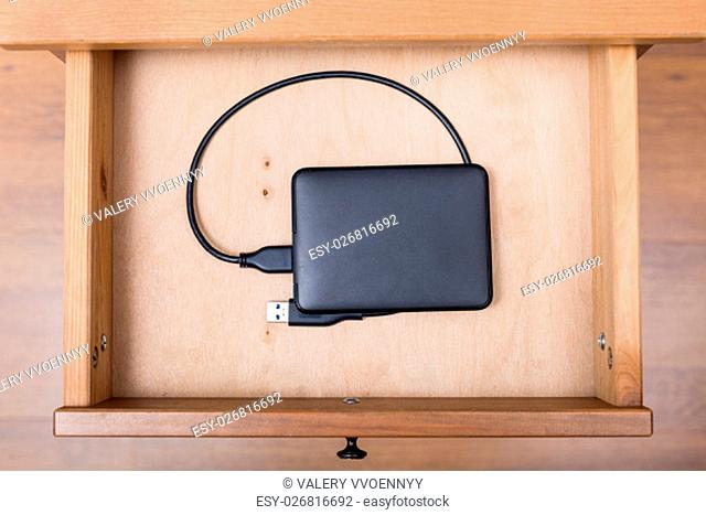 top view of external computer hard drive in open drawer of nightstand
