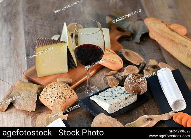 Tasty homemade slices of white cheese and fresh crusty bread with bottle and glass of red wine on rustic wooden table