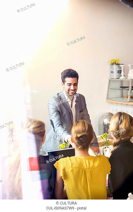 Rear view of young women sitting infront of laptop and young man wearing suit jacket standing smiling
