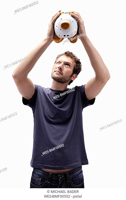 Young man holding piggy bank, portrait