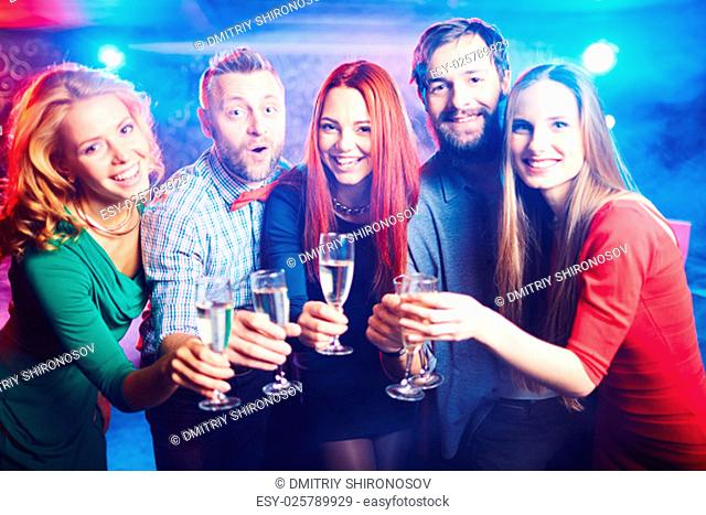 Group of ecstatic friends having party in night club