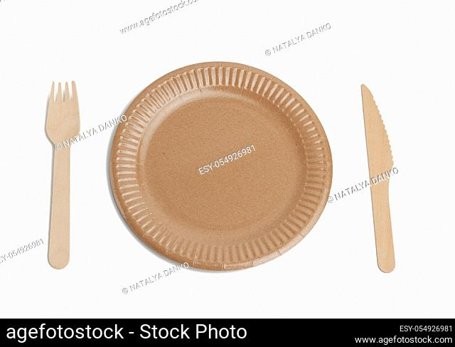 wooden fork, knife and empty round brown disposable plate made from recycled materials isolated on white background, top view