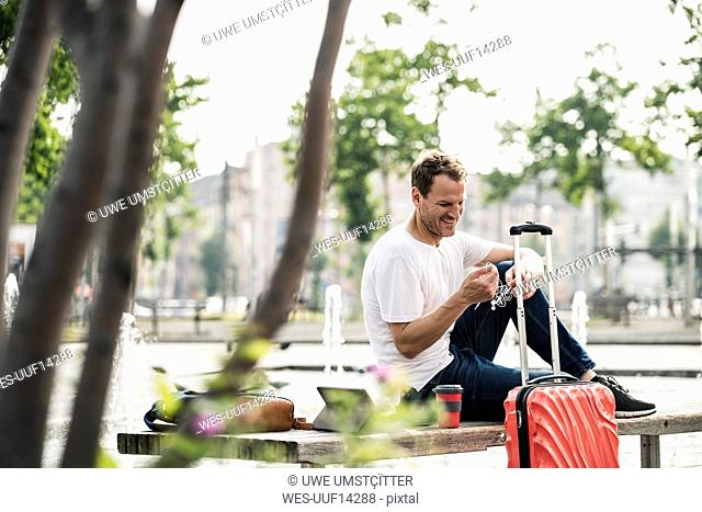 Smiling man with rolling suitcase sitting on bench