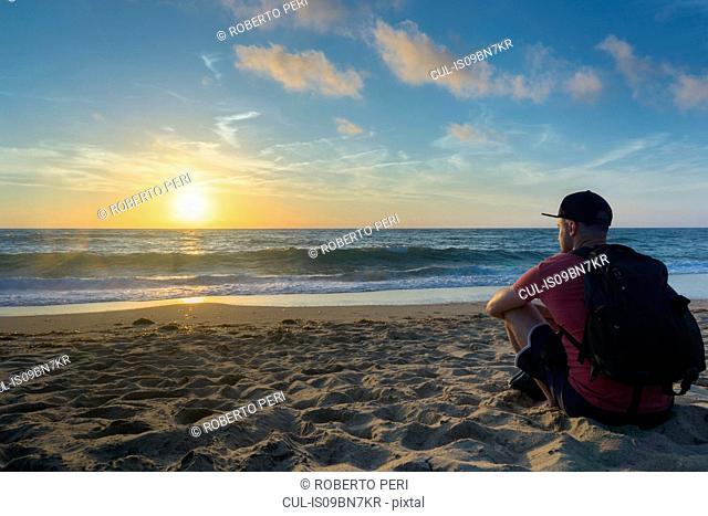 Man enjoying sunset on beach