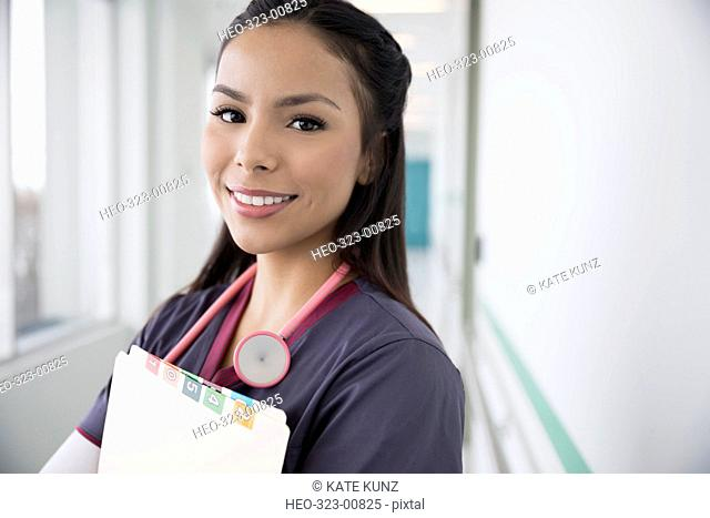 Portrait smiling female nurse with medical records in clinic corridor