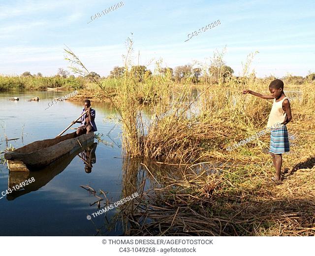 Namibia - Kavango girl fishing at the riverbank and boy in his fishing boat on the Okavango River  Caprivi region, Namibia
