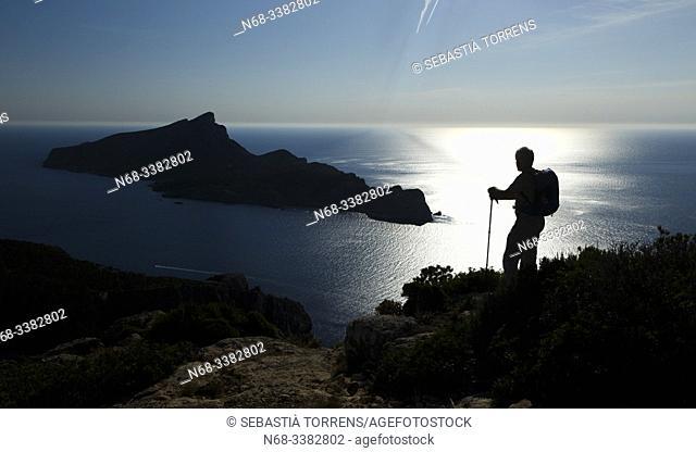 Backlight view of the island of Sa Dragonera from Andratx coast with hiker, Mallorca, Spain