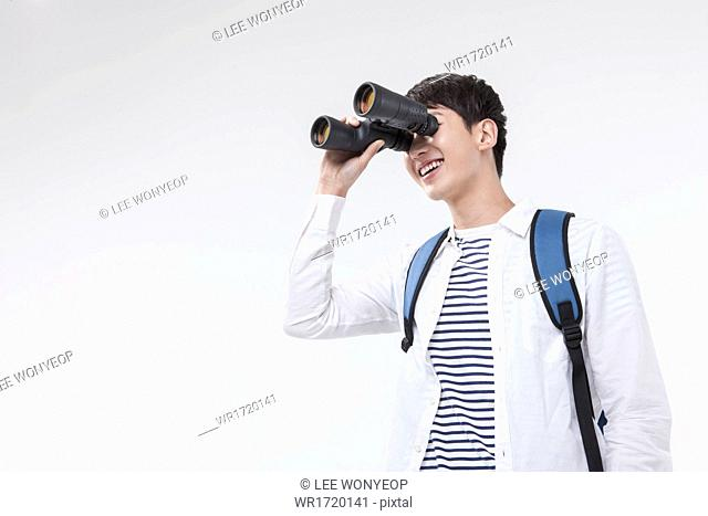 A man looking with binoculars