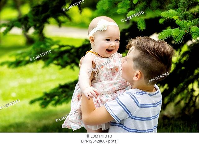 A young boy is playing with his baby sister and holding her in the air in a city park on a warm summer day; Edmonton, Alberta, Canada