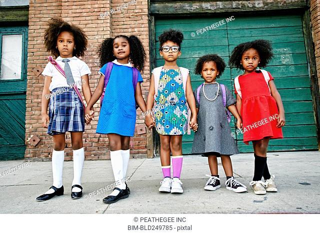 Serious girls posing on city sidewalk