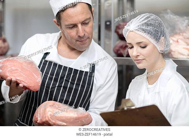 Man and woman with meat and clipboard in storehouse of a butchery