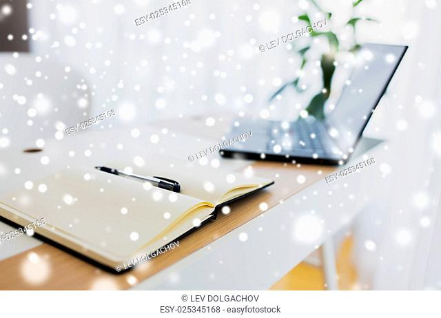 business, objects and education concept - notebook or diary with pen and laptop computer on office table over snow