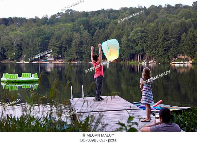 Girl standing on jetty releasing sky lantern, young girl watching, woman photographing event using smartphone