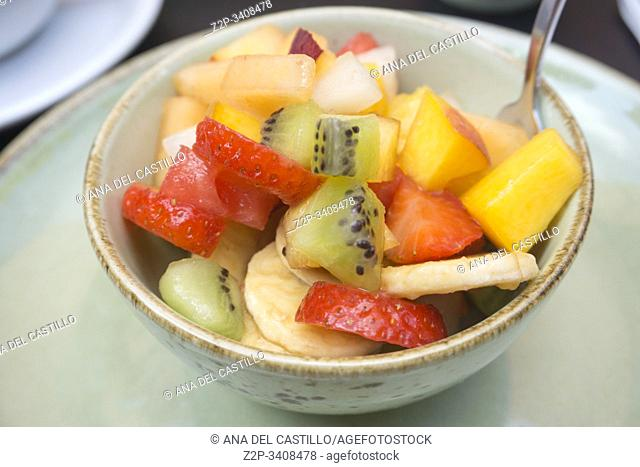 Sliced summer fruits on a green bowl
