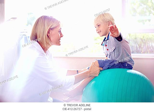Physical therapist holding boy with arms outstretched on fitness ball