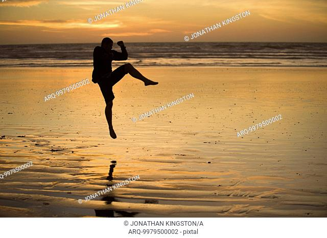 One mid adult man practices Taekwondo on the beach at sunset in Morro Bay, California