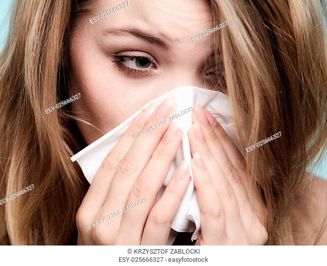 flu cold or allergy symptom. sick woman girl sneezing in tissue on blue. health care