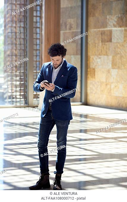 Man text messaging while walking through lobby