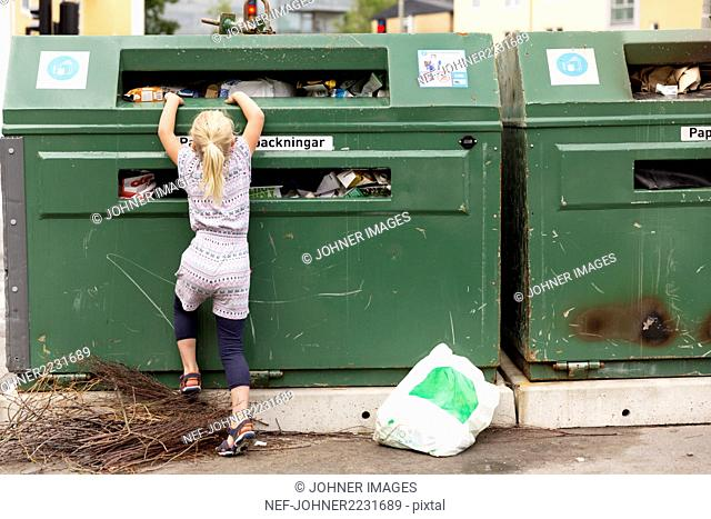 Girl throwing rubbish into recycling bin