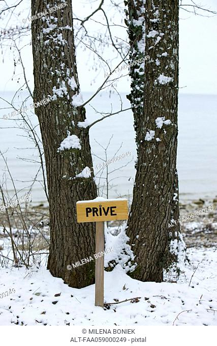 Wintery scene with sign reading private in French