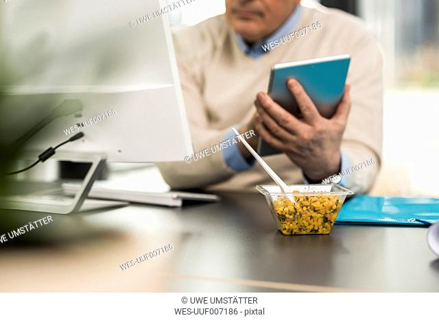 Senior man in office, holding digital tablet, salad in plastic bowl on desk