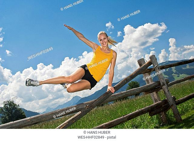 Austria, Salzburger Land, Young woman jumping over fence