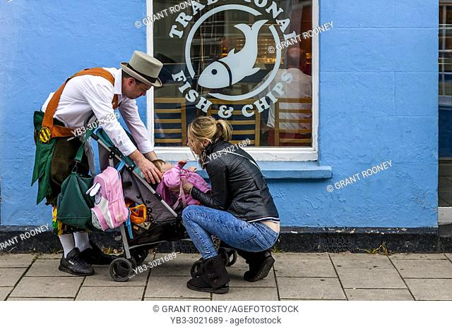 A Morris Man Helps Put A Baby In A Pushchair During The Annual Lewes Folk Festival, Lewes, Sussex, UK