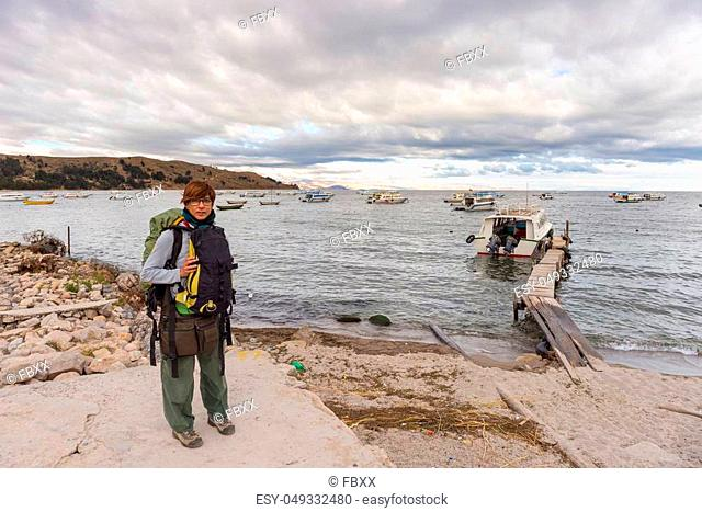 One person with backpack waiting for boat at Copacabana pier on Titicaca Lake, among the most scenic travel destination in Bolivia