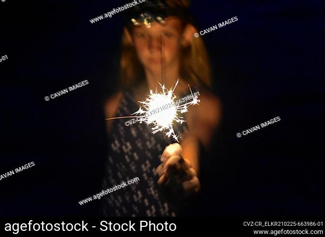 Girl holding a bright sparkler in her hand