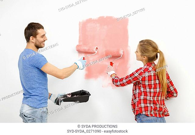 happy couple painting wall at home