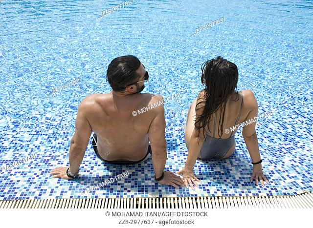 Happy couple relaxing in the swimming pool