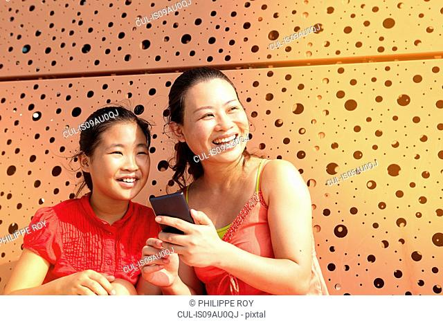 Mid adult woman and daughter using smartphone