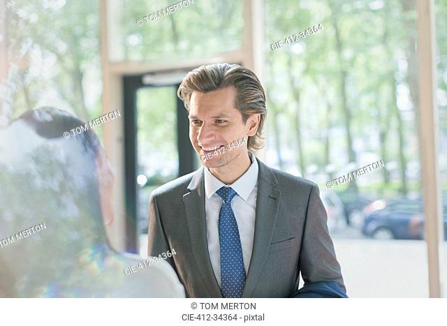 Smiling businessman talking to businesswoman in lobby