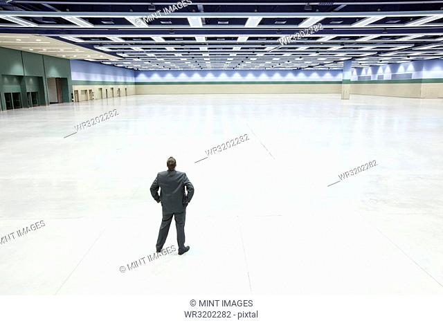 A view looking down on a single businessman surveying the interior of a convention centre arena