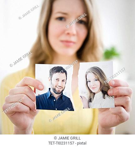 Woman holding torn photograph