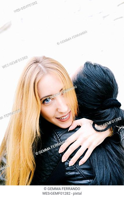 Portrait of young woman hugging her friend in front of white brick wall