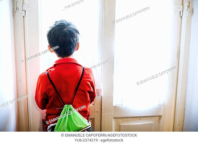 Child with rucksack looks out a window