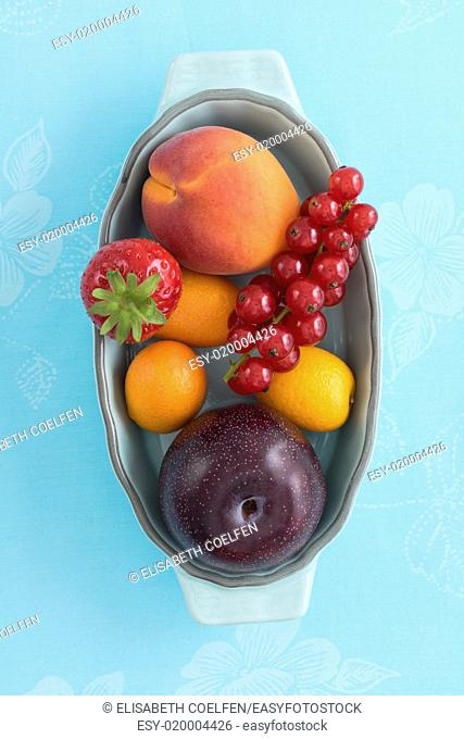 Overhead shot of a collection of different summer fruits in a bowl