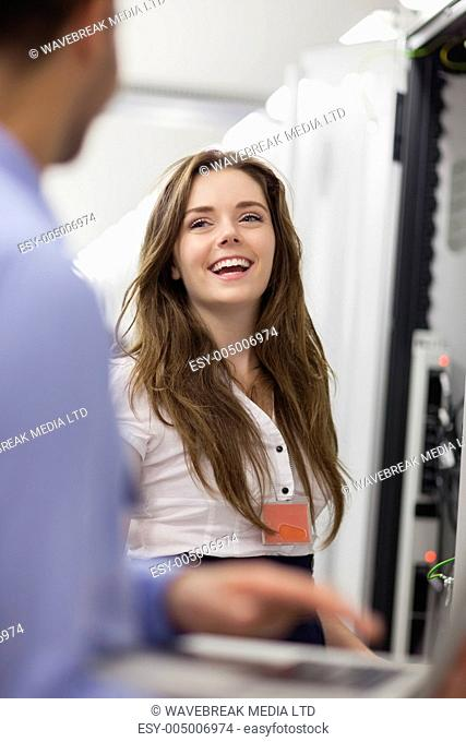 Woman working on servers laughing with colleauge in data center