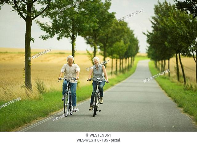 Senior couple biking on country road