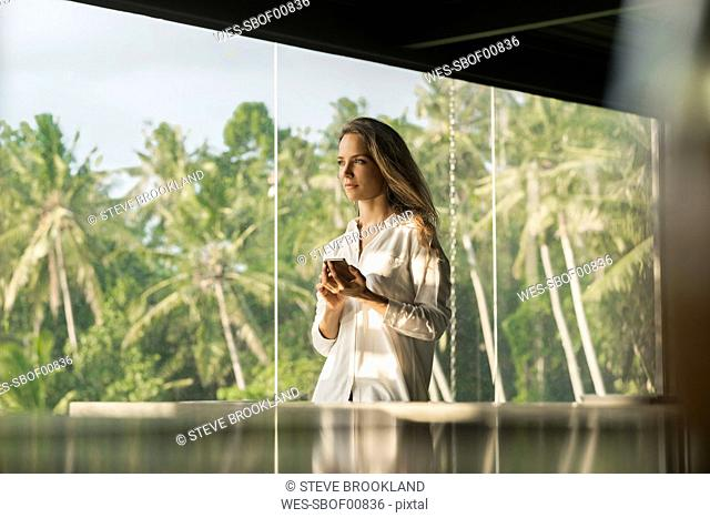 Woman holding smartphone in design house in front of lush tropical garden