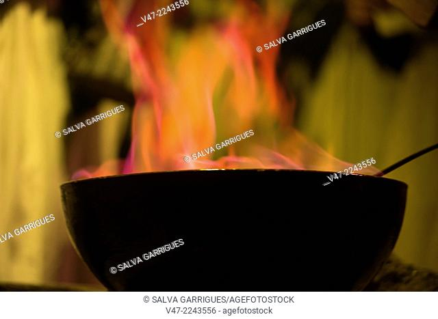 A monk takes the spell of the typical queimada traditions and Galician cuisine, Galicia, Spain
