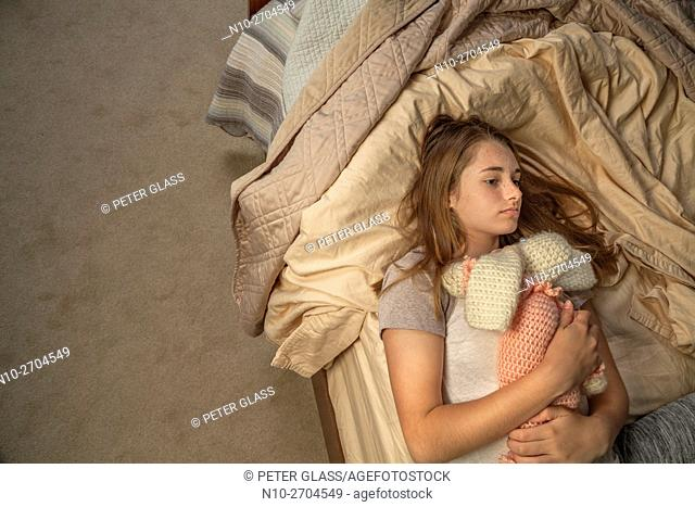 Teenage girl lying down in bed, holding a doll